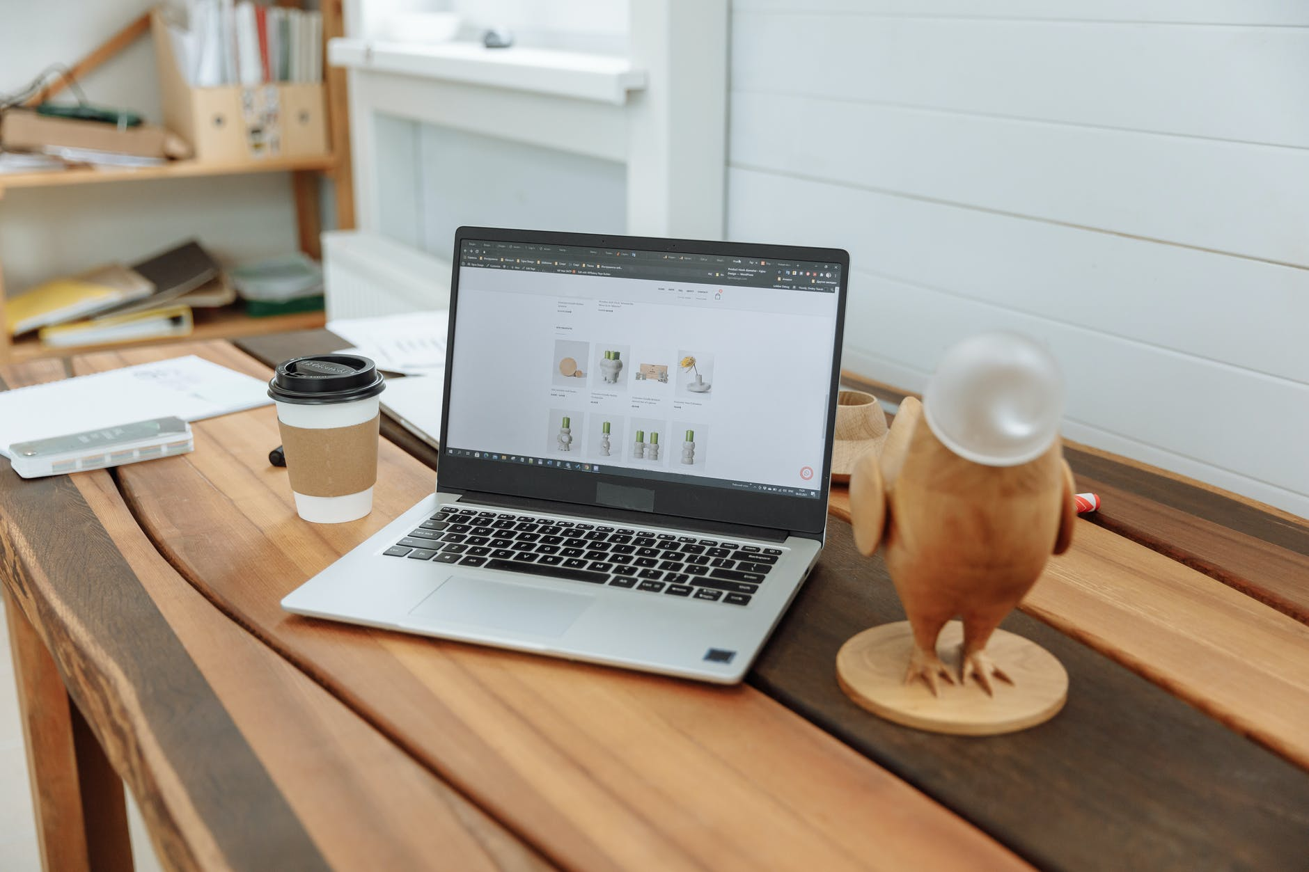 laptop on a wooden table with the design business website on the screen